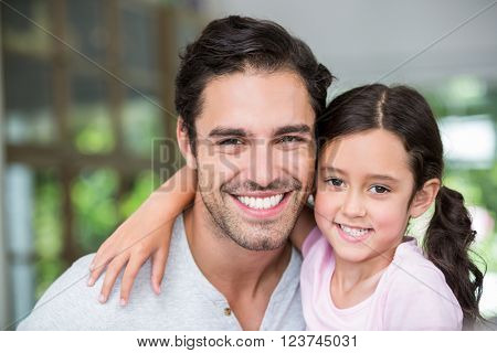 Portrait of smiling father and daughter with arm around at home
