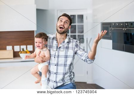 Frustrated father holding crying baby boy at table in kitchen