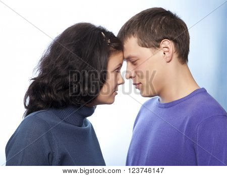 Beautiful loving young couple smiling against a blue background