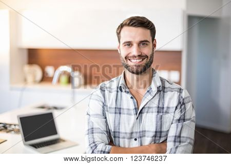 Portrait of confident young man standing by kitchen counter