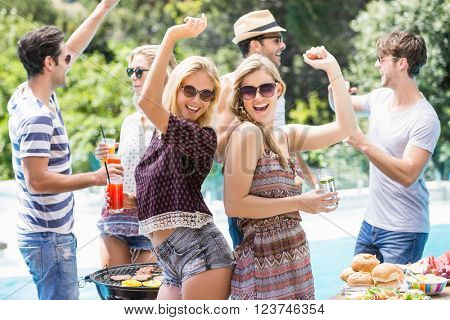 Group of friends dancing at outdoors barbecue party near pool