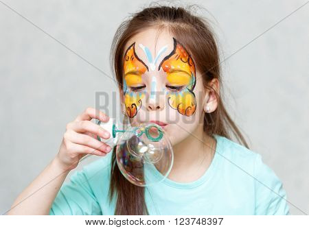 Portrait Of Cute Little Girl Blowing Triple Soap Bubble