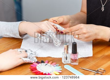 Manicure process: nails wrapped in foil in salon