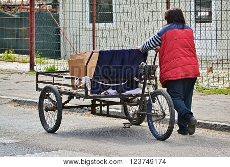 Poor woman pushing an old three wheel cart on the street