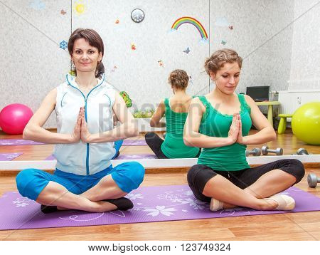 Sporty Young Women In Namaste Yoga Position In Fitness Studio