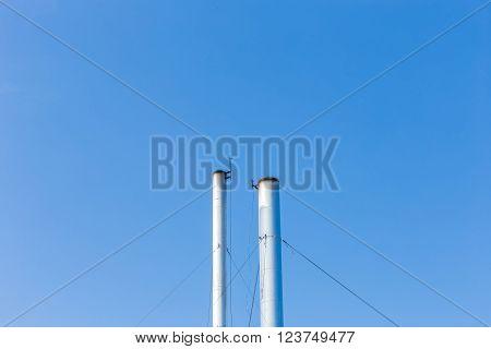 Two smokestacks on blue sky background in Phuket, Thailand