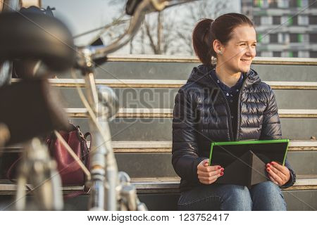 Smiling young woman student taping on tablet using tablet in a city park sitting on stairs near a bicycle.Young smiling student outdoors with tabletand bycicle.Life style.City