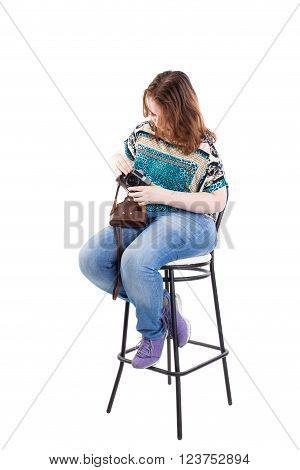 Beautiful redhead plus size model holding retro camera in leather case and sitting ot the bar chair. Isolated on a white background.