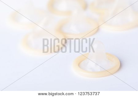 Ground rolled latex condoms on white background