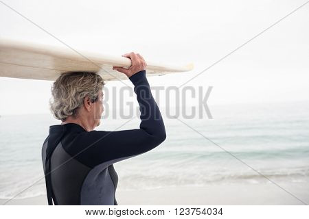 Senior woman in wetsuit carrying surfboard over head on the beach