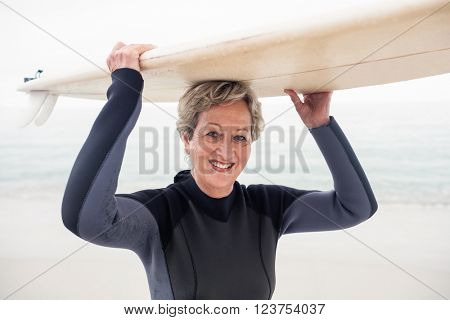 Portrait of senior woman in wetsuit carrying surfboard over head on the beach