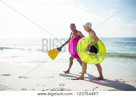 Happy senior couple walking on beach with inflatable rings and flippers on a sunny day