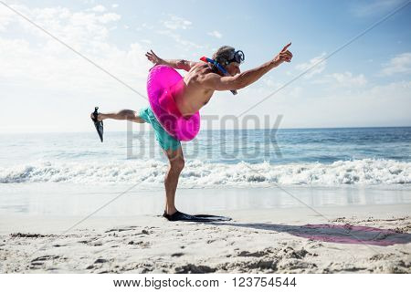 Senior man with scuba gear and inflatable ring enjoying their holiday on beach