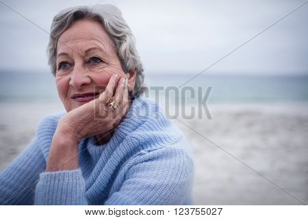 Thoughtful senior man sitting on the beach on holidays