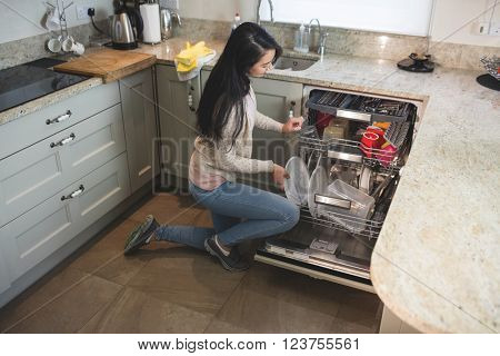 Woman in kitchen arranging plates in dish washer