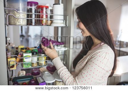 Young woman picking a bottle from storage cabinet in kitchen