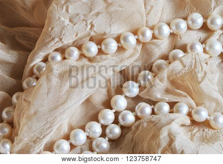 pearl beads on beige draped fabric background