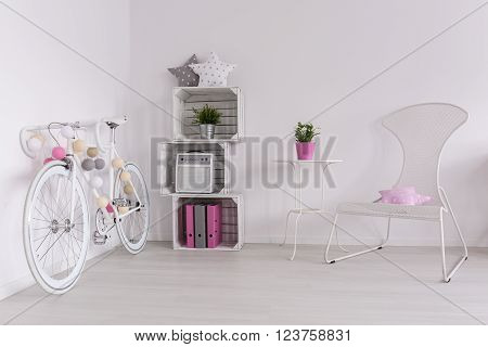 White bike, DIY bookcase and white chair in spacious interior