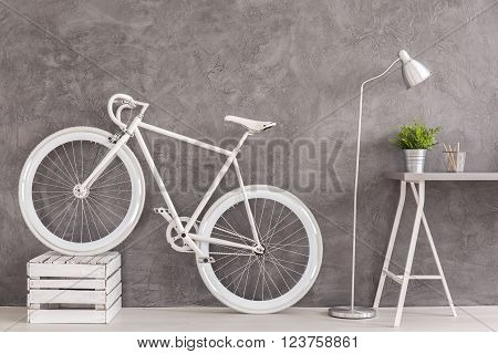 Grey interior with white bike, lamp and simple desk