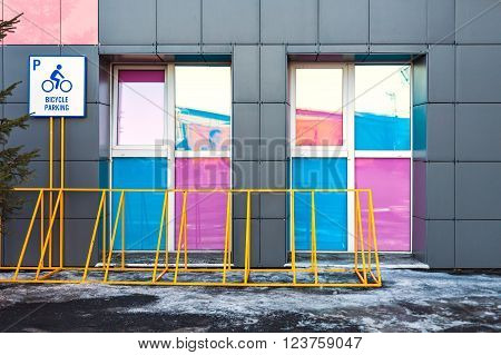 Blank yellow sign with Bicycle parking. Bicycle parking at the background of gray buildings with large windows pink. Healthy lifestyle. Season