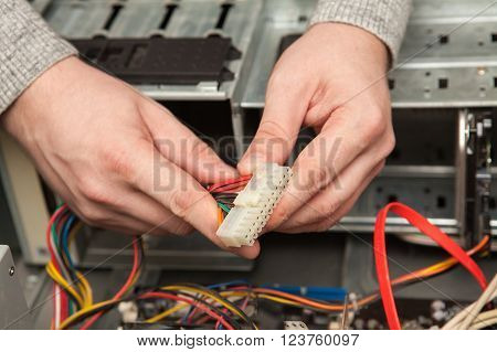 Technician Holding A Cable From The Power Supply.