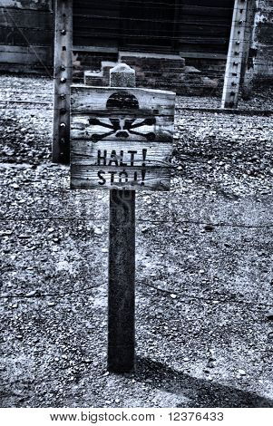 old style photo of Caution sign board in Auschwitz concentration camp, Poland
