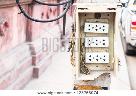 Wall plug on power pole on the side of the road.