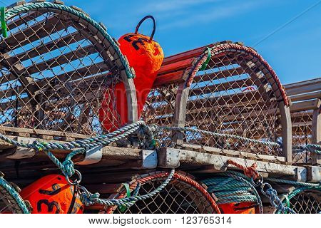 Colorful fisherman buoys laying in a lobster trap on a wharf in Prince Edward Island, Canada.