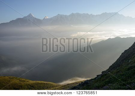 Ridges enshrouded in everpresent mist and fog Caucasus Mountains Georgia. Sunbeams penetrate fog. Alpine meadow and flowers in foreground.