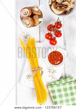 Italian spaghetti, champignon, dry mushrooms, tomato sauce, fresh cherry tomatoes, and spices on a wooden background, pasta ingredients, top view, copy space, horizontal