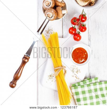 Italian spaghetti champignon dry mushrooms tomato sauce fresh cherry tomatoes and spices on a wooden background pasta ingredients top view copy space horizontal