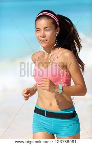Happy running woman listening to music with earphones and fitness watch activity tracker in sportswear and sports bra. Healthy Asian runner girl on beach with wearable tech gear.
