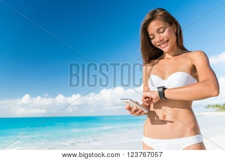 Bikini woman using smart phone syncing watch data for smartwatch app on smartphone. Happy Asian girl on beach summer holidays in tropical destination looking at screen of activity tracker device.