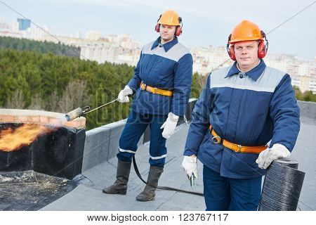 Flat roof workers with bitumen roofing felt and flame torch