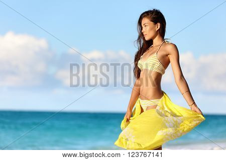 Sexy Asian woman with a slim stomach bikini body relaxing in sunset with yellow pareo cover-up swimwear and beachwear enjoying her weight loss on beach summer vacation in the Caribbean.