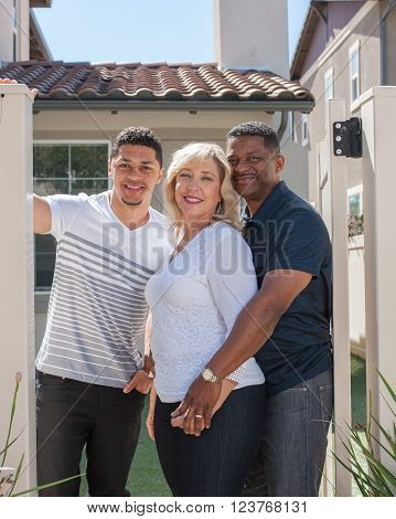 Closer view of multiracial family posing in yard featuring mom.