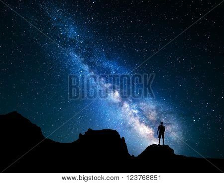 Landscape with Milky Way. Blue night sky with stars and silhouette of a standing happy man on the mountain.