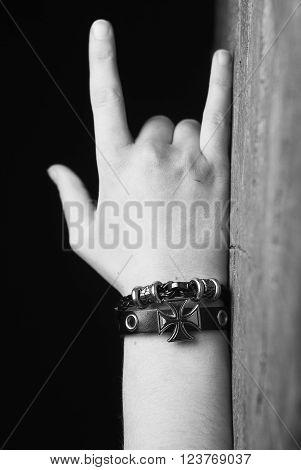Female hand devil horns metal rock gesture sign symbol and leather bracelet with cross on black background