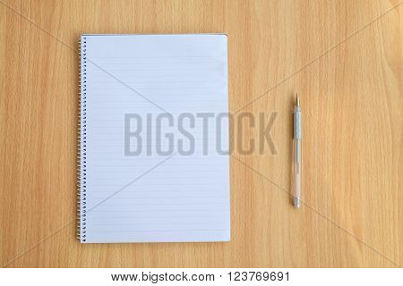 Opened notepad and pen on wooden table