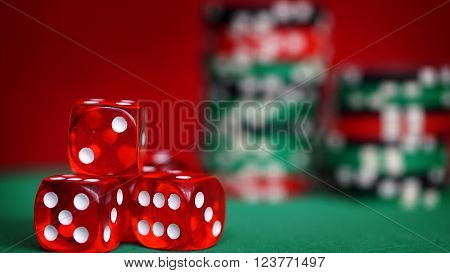 The red casino dice and casino chips on green table