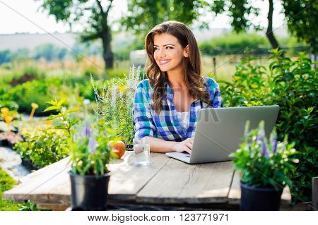 Beautiful gardener with notebook sitting at the table, managing supplies, green sunny nature