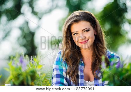 Beautiful young gardener holding seedling in flower pot, sitting at the table, green sunny nature