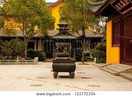 An incense burner and traditional Asian architecture at Futian Jing Temple in Sijing Ancient town located in Songjiang district of Shanghai China.