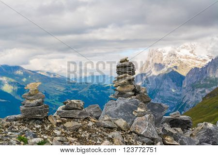 Small cairn with snow alpine mountains at background