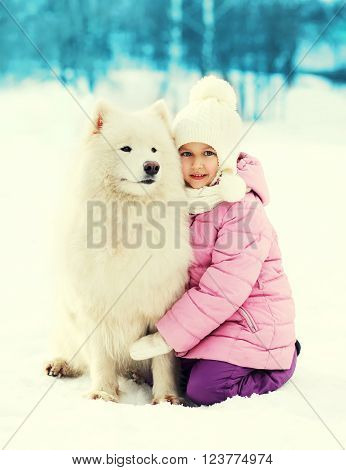 Little Child Hugging White Samoyed Dog On Snow In Winter Park