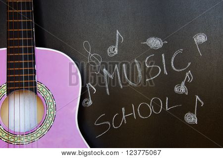 Music school for children with purple guitar closeup on blackboard background