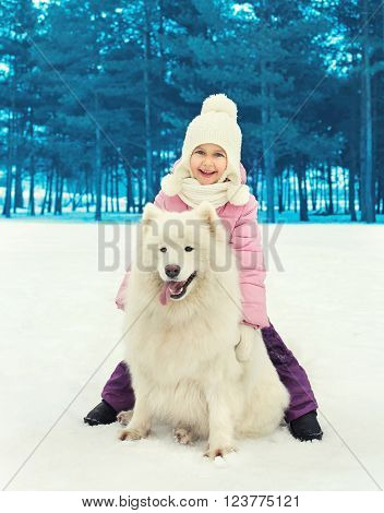 Happy Smiling Child With White Samoyed Dog On Snow In Winter Day