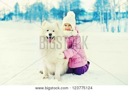 Happy Smiling Child With White Samoyed Dog Playing On Snow In Winter Day