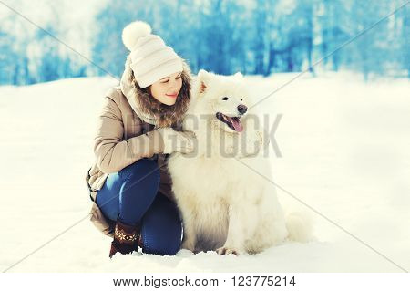 Woman Owner Hugging White Samoyed Dog In Winter Park