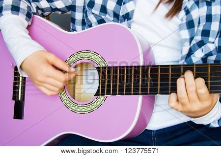 Music school for children with purple guitar closeup and child playing